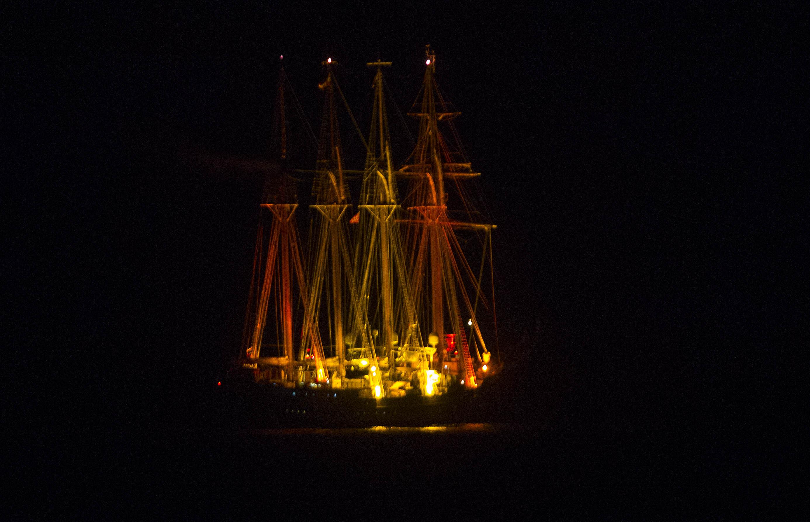 El Juan Sebastián de Elcano iluminado con la bandera de España, fondeado en la Bahía. Foto: Antonio Vázquez