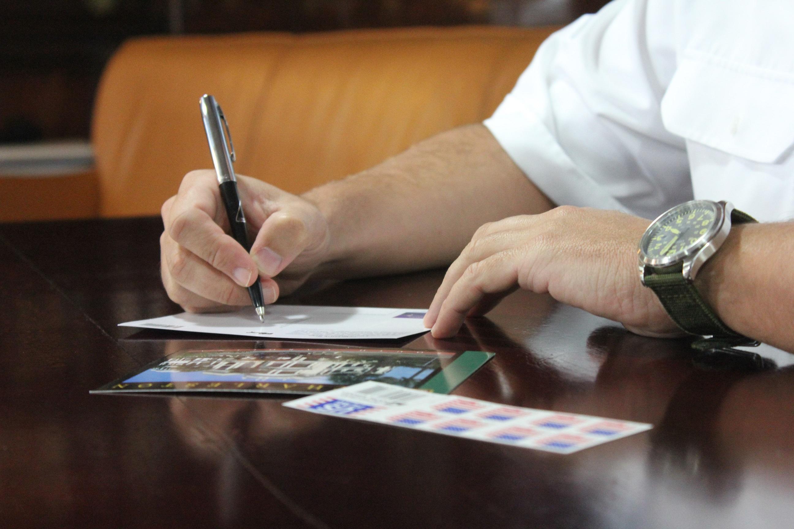 Un miembro de la dotación del Elcano escribe una postal. Foto: Armada Española